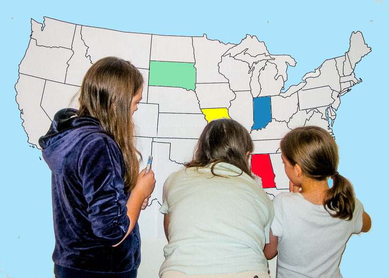 Finding states on a large wall map of the United States.